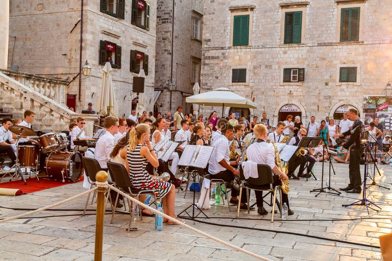 City view of people in the old town at the town square looking at musicians holding a free outdoor concert in Dubrovnik. royalty free stock images