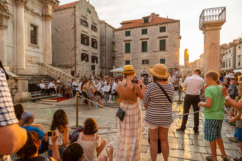 City view of people in the old town at the town square looking at musicians in Croatia. stock photos