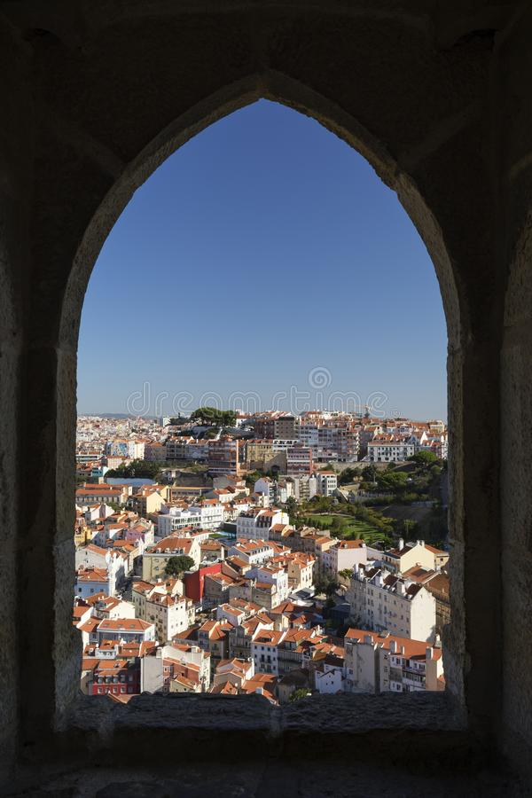 City viewed through castle`s window in Lisbon. Historical downtown viewed through an old window at the Sao Jorge Castle Saint George Castle, Castelo de Sao Jorge royalty free stock photography