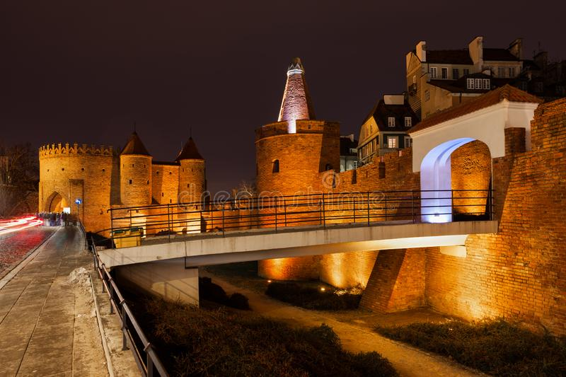 City Wall Fortification in Old Town of Warsaw. Poland, Warsaw, city wall fortification with the Barbican illuminated at night, footbridge and gate to the Old royalty free stock images