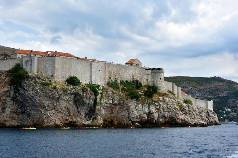 City wall of Dubrovnic. City wall at rocky coast of Dubrovnik, Croatia.Always there are many tourists walking over the wall stock images