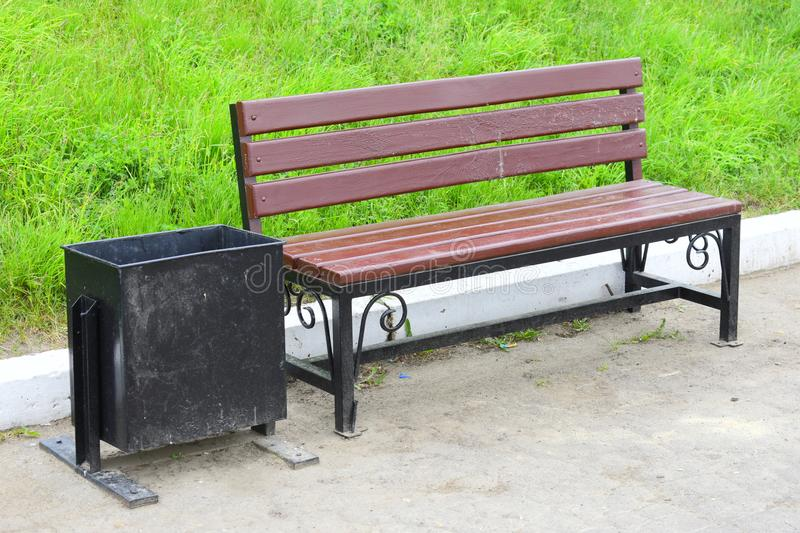 City wooden bench with forged metal base is used in parks stock photos
