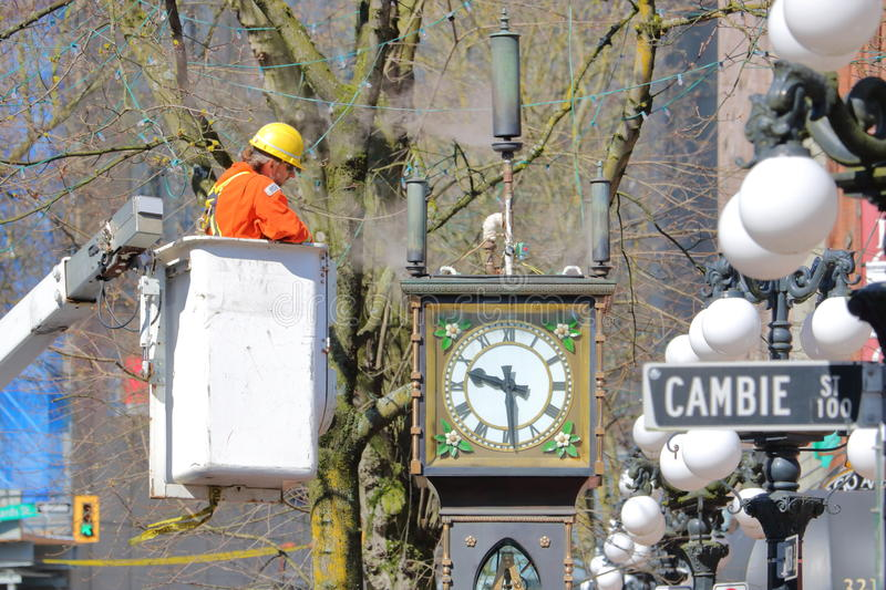 City Worker Repairs Vancouver Steam Clock. Close on a city worker cleaning and fixing the famous steam clock in Vancouver`s Gastown district in preparations for royalty free stock image