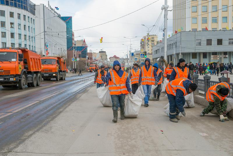 City workers collecting garbage in the city center on a nasty day stock image