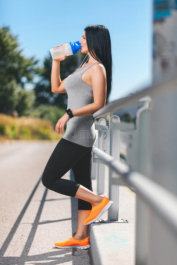 City workout. Beautiful woman with a smartwatch training in an urban setting stock images