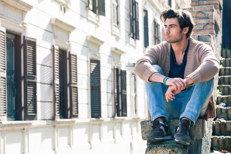 City young handsome man. Urban sitting model. Building windows stock image