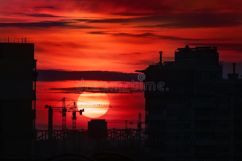 Citysacpe silhouette of buildings and construction site cranes with big bloody fiery red sun at dusk on background. Scenic. Industrial landscape sunset sky royalty free stock images