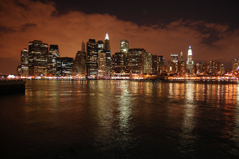 Cityscape. This is a night photo of the New York Skyline from the Brooklyn side of the river. The storm clouds looming overhead add Character to the photo stock image