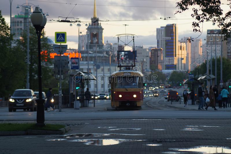 Cityscape. Alley, puddles, clouds, tram, cars, headlights. royalty free stock photography