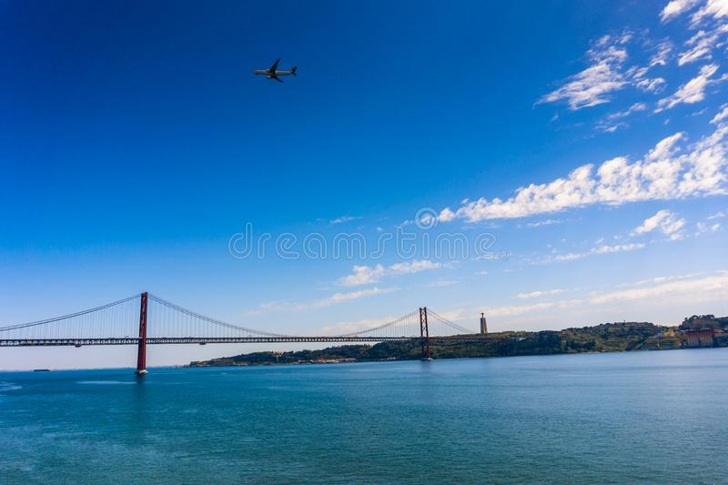 Cityscape with 25 April Bridge over the Tagus river and airplane in Lisbon royalty free stock photos