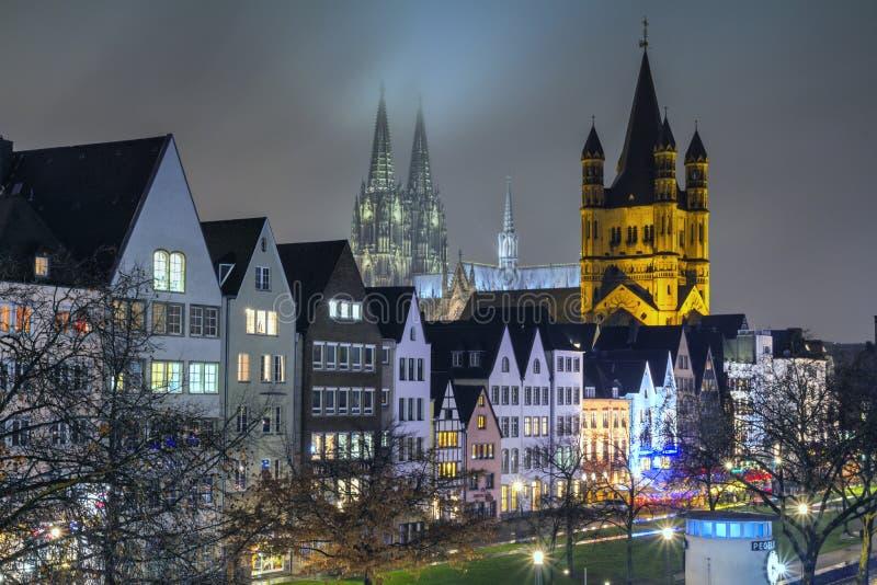 Cityscape - avondmening over de Rijn-promenade op achtergrond de Grote Heilige Martin Church en de Kathedraal van Keulen stock fotografie