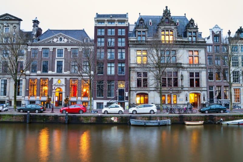 Cityscape - avondmening van de huizen met feestelijke decoratie en het stadskanaal met boten, stad van Amsterdam stock fotografie