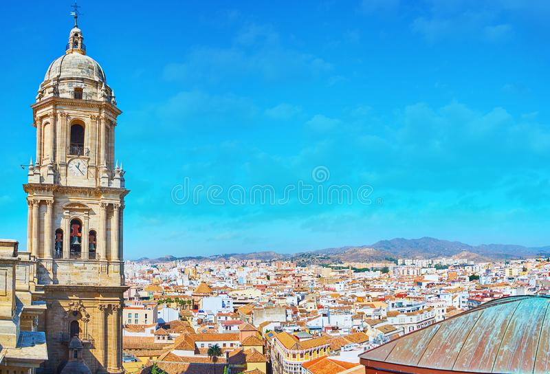 The cityscape with bell tower of Malaga Cathedral, Spain. The bell tower of Malaga Cathedral in front of the tile roofs of the old town, Andalusia, Spain stock photos