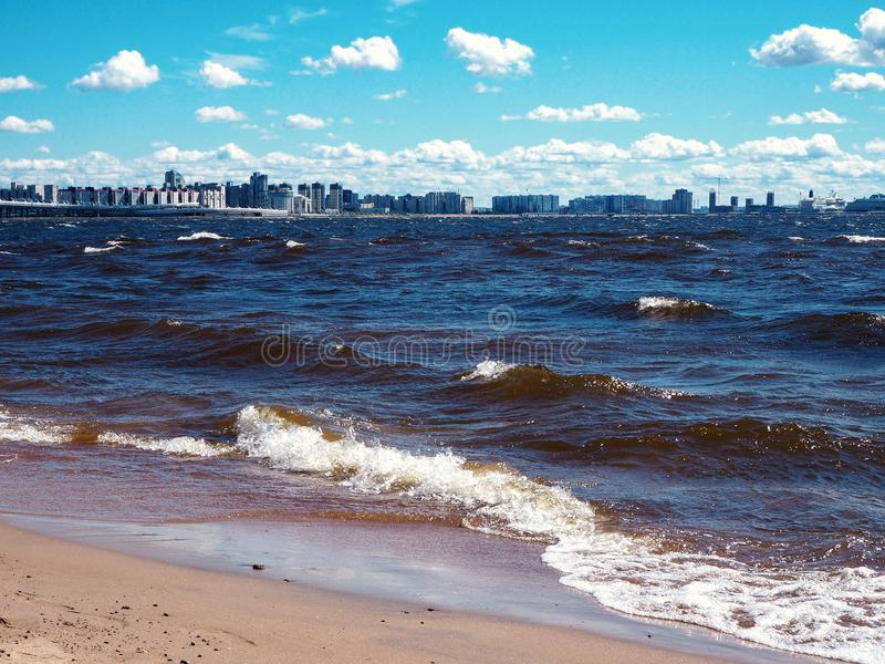 Cityscape of breaking waves with foam ran to the sandy beach during a storm. At the beautiful summer sea shore background with coastal city skyline at the royalty free stock images