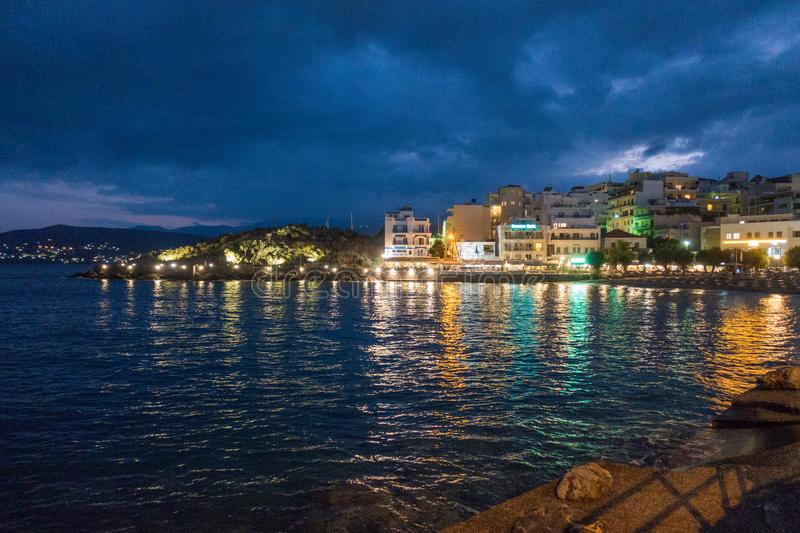 Cityscape and sea at night. Cityscape of buildings against sea at night in Nikos Agiolaos, Crete, Greece royalty free stock photography