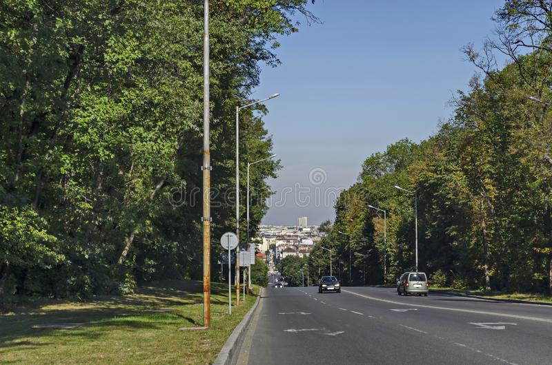 Cityscape of bulgarian capital city Sofia from the street through forest toward central residential district. Bulgaria, Europe royalty free stock photography