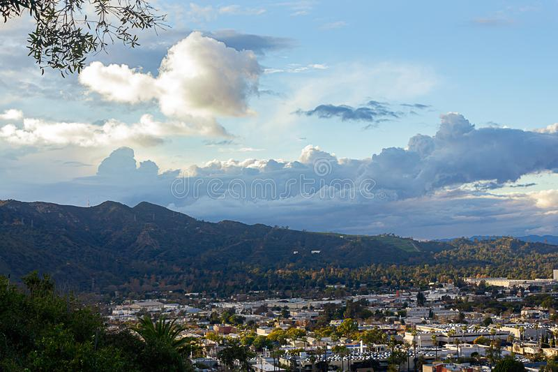 Cityscape, clooudscape with mountain range seen from a hilltop greenery. After a storm stock image