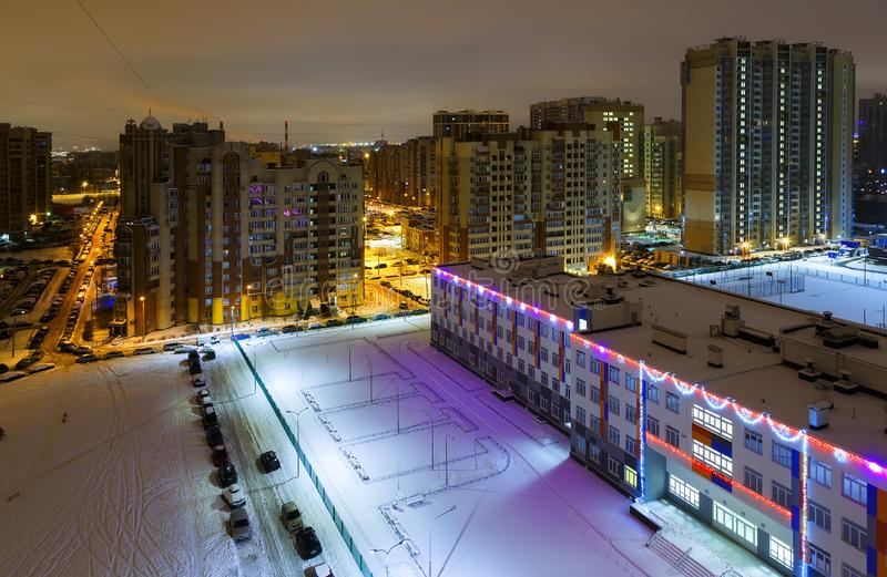 Cityscape of dormitory area of Saint Petersburg, Russia. Residential apartment and public buildings decorated with Christmas lights. Streets and car parking royalty free stock photos