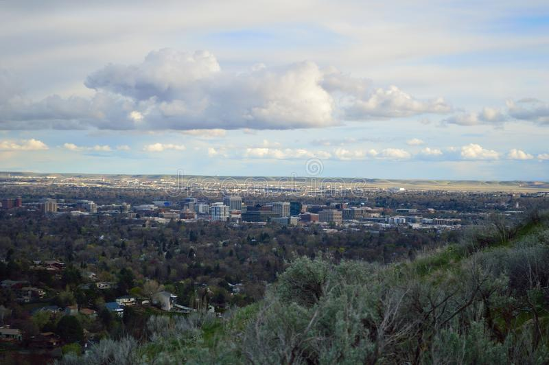 Cityscape of Downtown Boise from the north foothills. Landscape of sun and shadow over the city on a cloudy spring evening stock photo