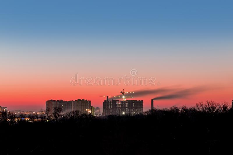 Cityscape with dramatic sky sunset. Silhouette of buildings and smoking pipes. Urban industrial city. Environmental pollution stock image