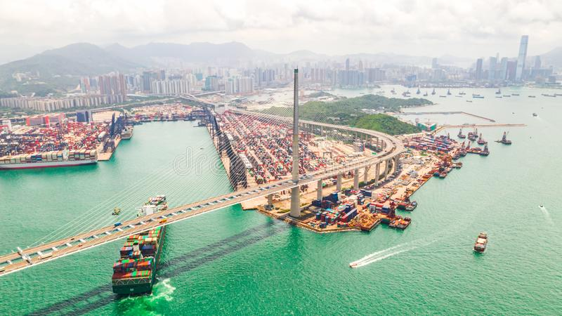 Cityscape drone aerial view of Hong Kong city, port industrial district, cargo container ship, cranes, car traffic on bridge. Cityscape drone aerial view of Hong stock images