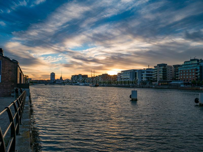 Cityscape of Dublin Ireland at sunset over River Liffey. With dramatic, vivid cloudy sky royalty free stock photography