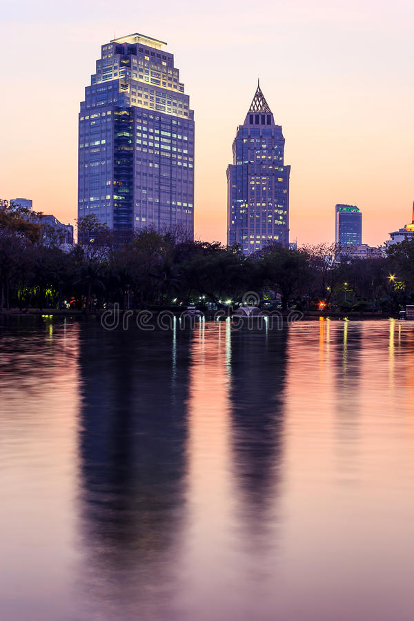 Cityscape at dusk. Two modern buildings with reflection at Lumpini garden at dusk stock images