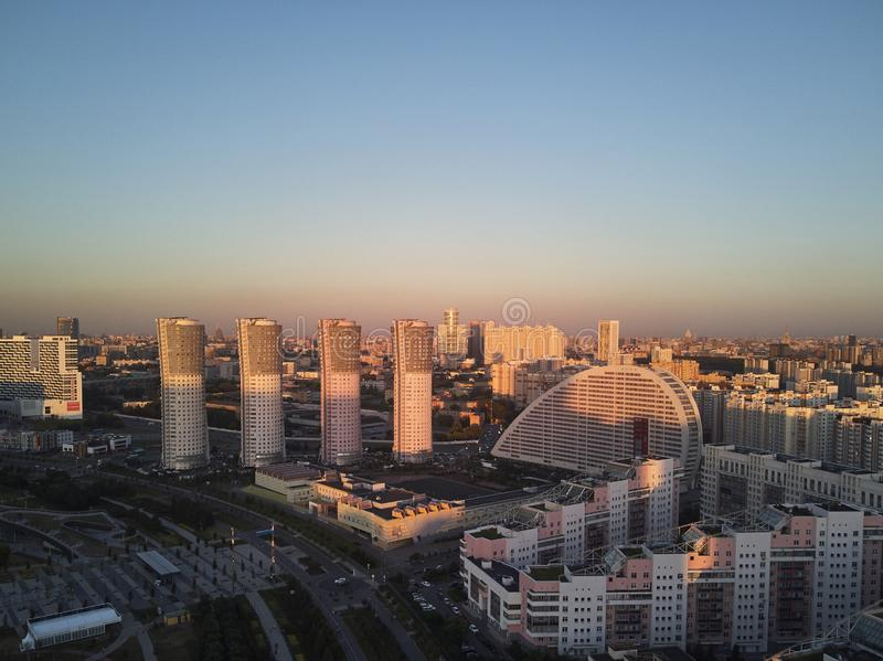 Cityscape with four high-rise residential buildings and city blocks in the evening. Aerial view.  stock photo