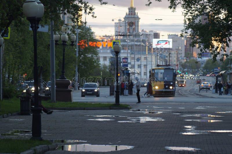 cityscape Gasse, Pfützen, Wolken, Tram, Autos, Scheinwerfer lizenzfreie stockbilder