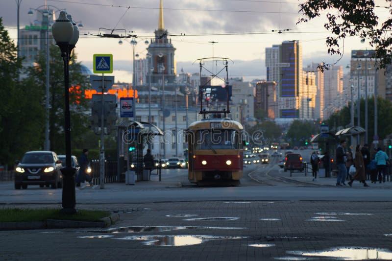 cityscape Gasse, Pfützen, Wolken, Tram, Autos, Scheinwerfer lizenzfreie stockfotografie