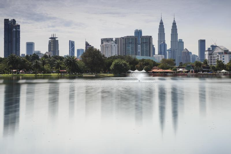 Cityscape of Kuala Lumpur at noon with Petronas Towers reflected on the Titiwangsa Lake.  stock images