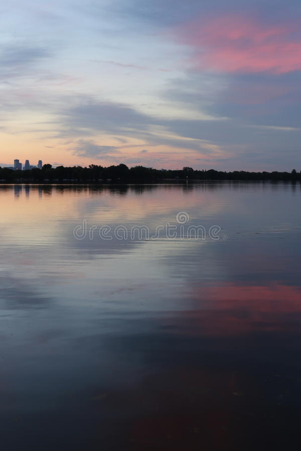 Cityscape and lake collide with the colors of the setting sun royalty free stock photo