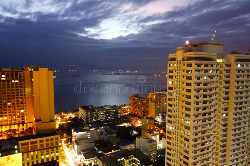 Cityscape Lighted High-rise Buildings Beside Calm Body of Water stock photo