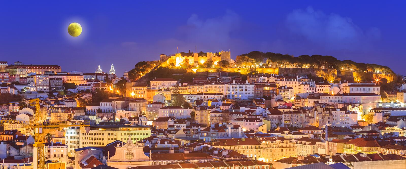 Cityscape of Lisbon at night. With full moon on the sky and illuminated architecture, in Portugal royalty free stock photo