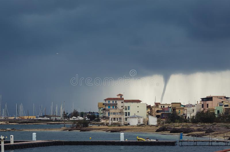 Cityscape of Marzamemi, province of Siracuse at stormy day. Tornado is at the background. Bad weather in Sicily royalty free stock photo