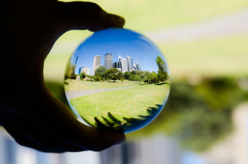 Cityscape mening met groene botanische tuin en blauwe hemelfotografie in de duidelijke bal van het kristalglas royalty-vrije stock afbeelding