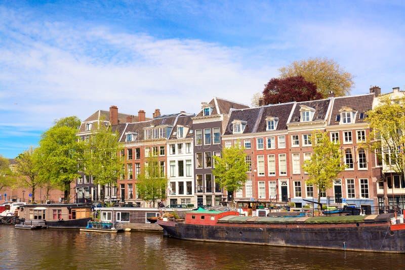 Cityscape mening van het kanaal van Amsterdam in de zomer met een blauwe hemel, huisboten en traditionele oude huizen Schilderach stock fotografie
