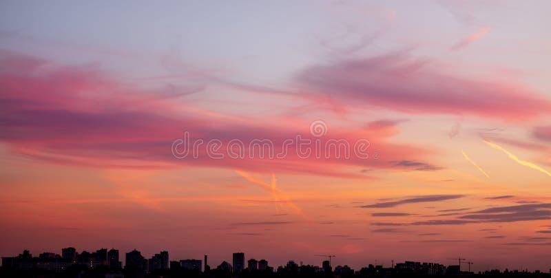 Cityscape met dramatische hemelzonsondergang Silhouet van gebouwen aand kranen bij bouwwerf Stedelijke industriële stadsachtergro stock afbeeldingen