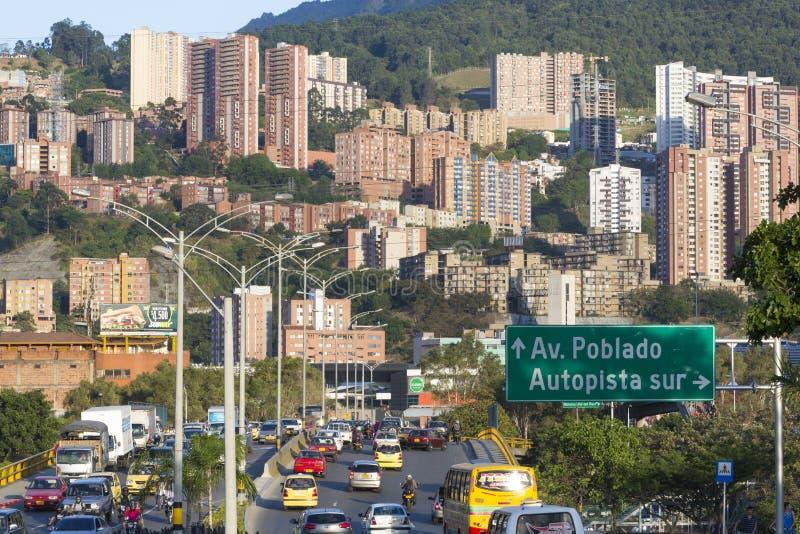 Cityscape och trafik på vägen med vägmärket till Poblado, Med royaltyfri foto