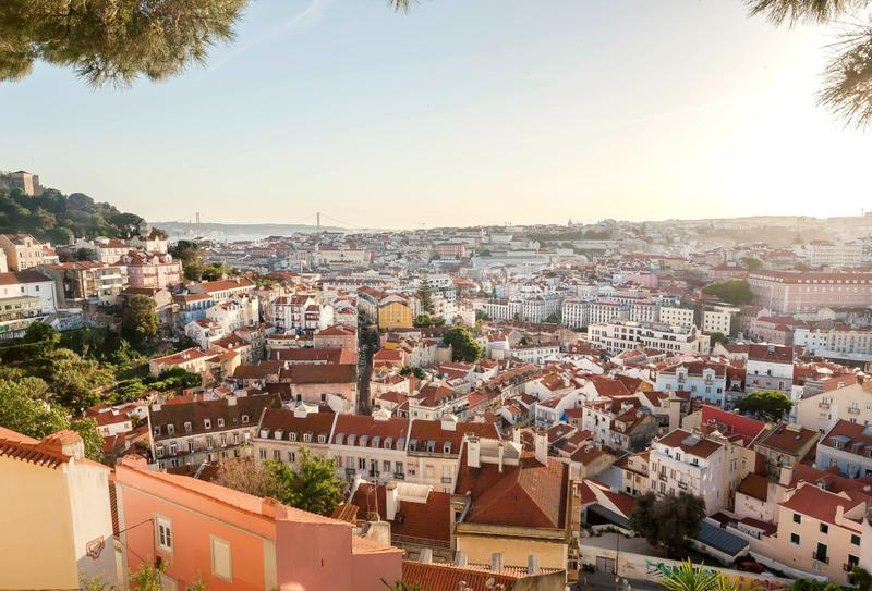 Cityscape of old capital with tile roofs and historical city streets at sunset. Cityscape of old capital with tile roofs and historical Lisbon streets at sunset royalty free stock photography