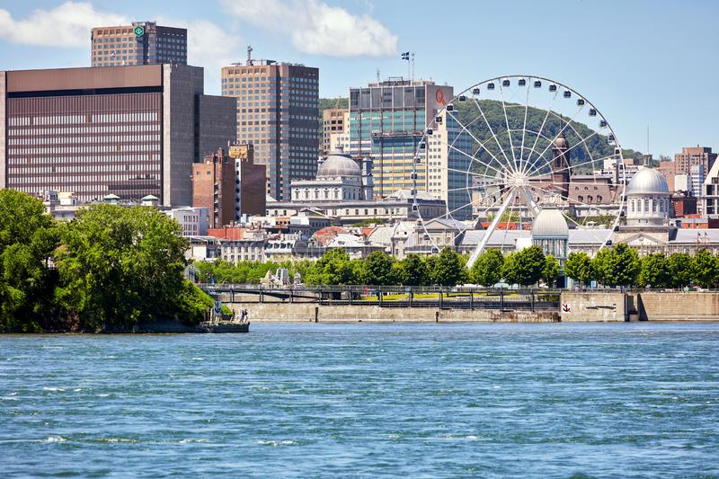 Cityscape of old port Montreal, Quebec, Canada, St. Lawrence river and ferris wheel royalty free stock photography