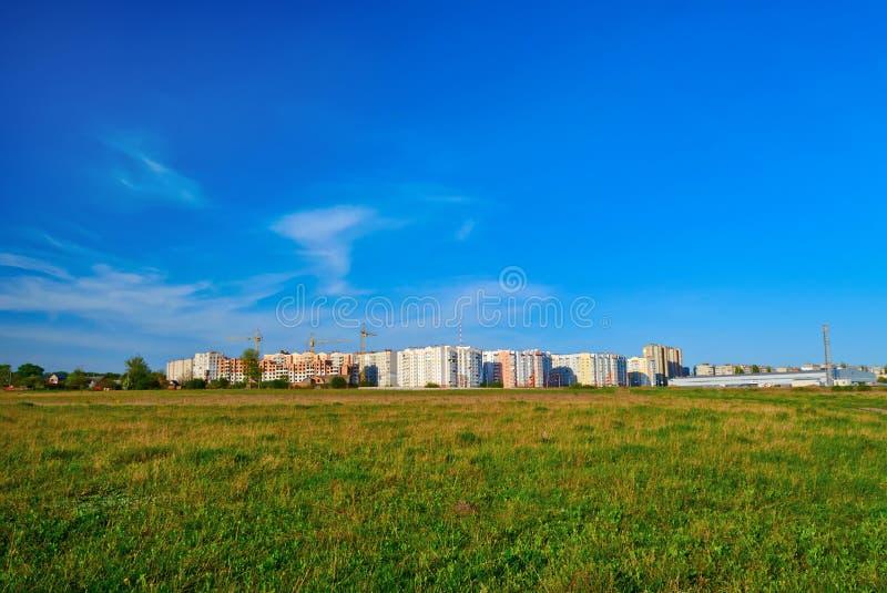 Cityscape op groen gras en blauwe hemel stock fotografie
