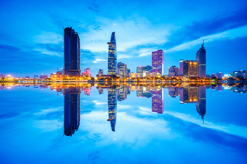 Cityscape in reflection of Ho Chi Minh city at beautiful twilight, viewed over Saigon river. royalty free stock photography