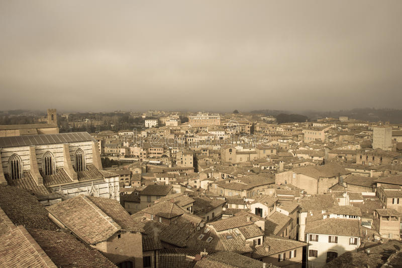 Cityscape of Siena with thick fog on background. Tuscany, Italy. Old polar effect. stock photo