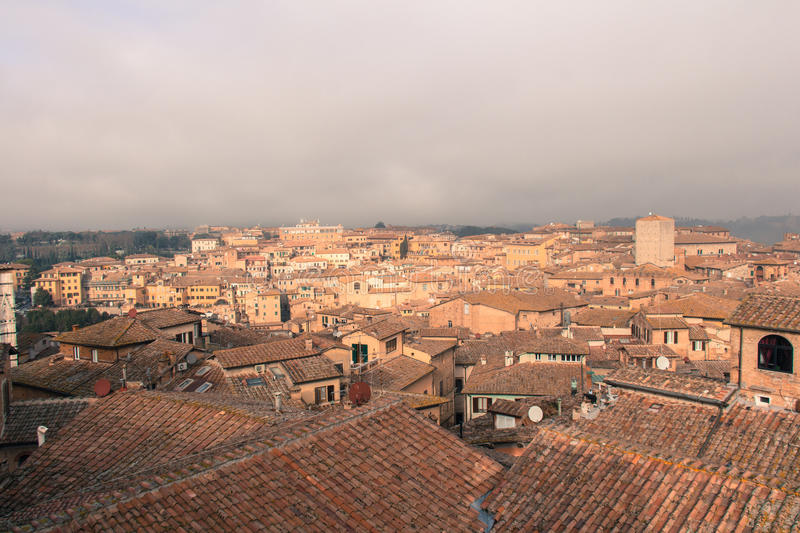 Cityscape of Siena with thick fog on background. Tuscany, Italy. royalty free stock photography