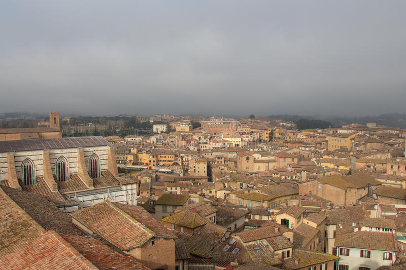 Cityscape of Siena with thick fog on background. Tuscany, Italy. stock photography