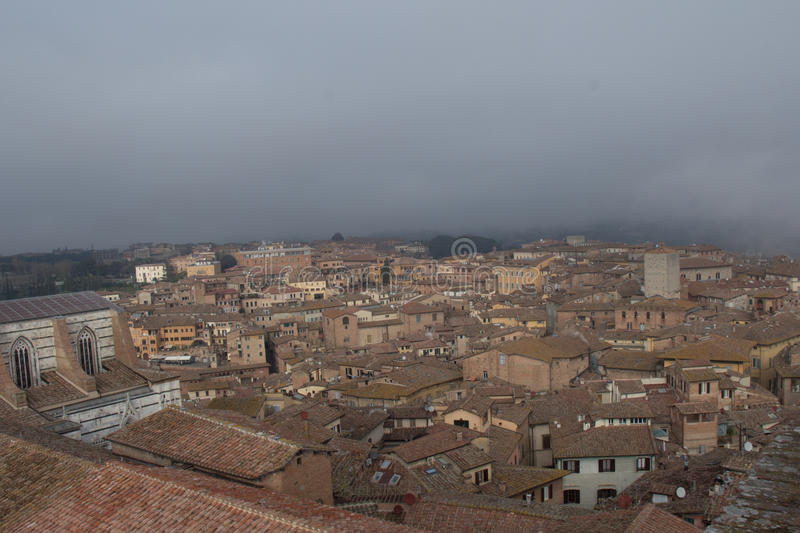 Cityscape of Siena with thick fog on background. Tuscany, Italy. stock photos