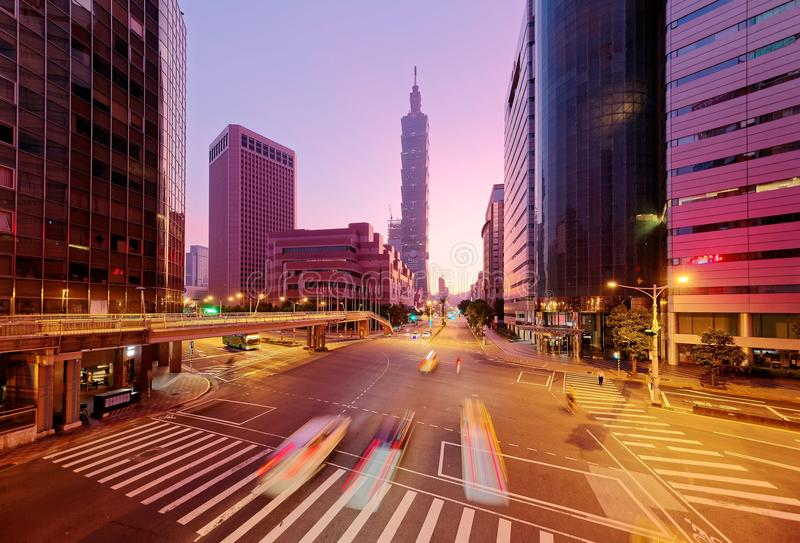 Cityscape of a street corner in Downtown Taipei City with traffic trails in morning twilight royalty free stock photography