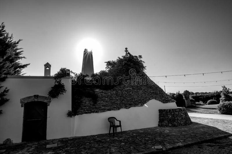 Typical truli architecture, Puglia. Italy. Cityscape with typical amazing architecture of truli with chimney light diffraction against the Sun in Puglia region royalty free stock photo