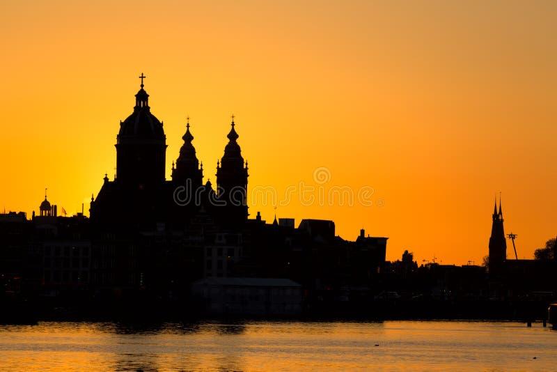 Cityscape van Amsterdam horizon met Kerk van Heilige Nicholas Sint-Nicolaaskerk tijdens zonsondergang Schilderachtig van Amsterda stock afbeelding